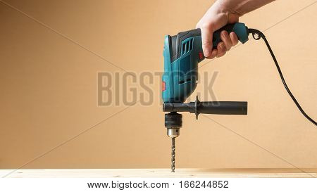Man holding green drill and drilling lining woods. Yellow orange copy space wall.