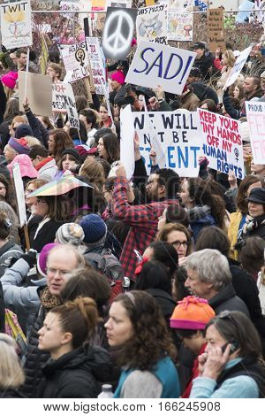 PHILADELPHIA, PA - JAN 21 2017: Women's March on Philadelphia. A sister march of Women's March on Washington. Women and men gathering in peaceful protest on Benjamin Franklin Parkway. Dense crowd shot with Sad sign and peace sign.