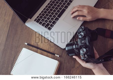 Camera on hand.Photographer workplace, Camera,Laptop,Memo on wooden desk.