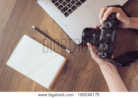 Photographer in workplace, Camera,Laptop,Memo on wooden desk.
