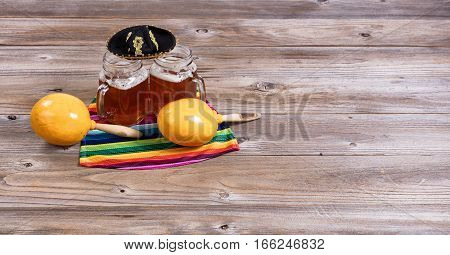 Cinco de Mayo concept with freshly poured beer maracas sombrero and placemat serapes on rustic table.
