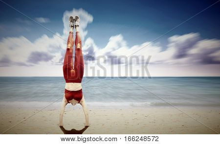 Women handstand at the beach with clody blue sky