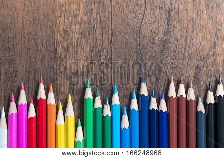 Color pencils on wood background. Art and writing concept.
