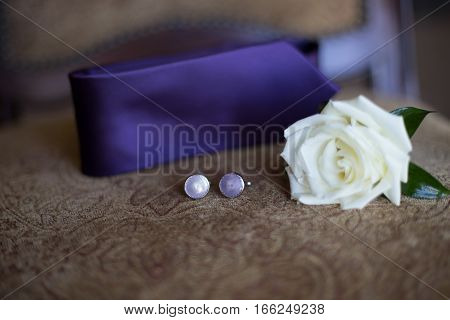 Groom's boutonniere attire purple and white on a brown background