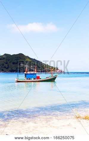 Colorful boat in bay at mountain background. Travel summer vacation and tropical beach concept. Vertical composition.