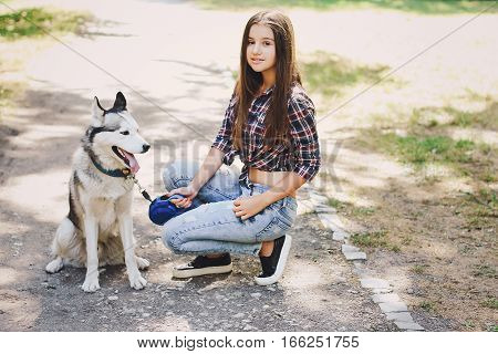 young beautiful girl walking park. good time. uses the means of communication. playing with the dog