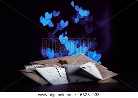 Valentines day letters, cards, blue glowing hearts in the dark