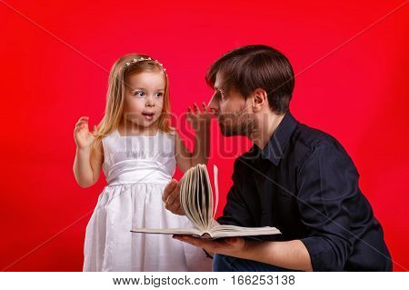 Father and daughter read a book. Girl emotionally reacts to an interesting story. Girl tells a tale wants. Tales on roles. The concept of home education.