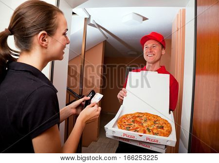 delivery boy presenting a hot pizza to a female customer at her door