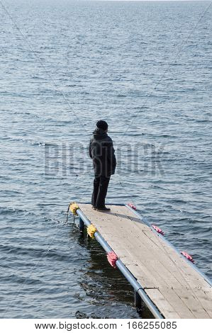 A man dressed in warm black clothing standing on a dock jutting into the blue gray waters of Lake Baikal in Siberia. He has his hands in his pockets and back to the camera.