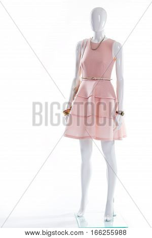 Salmon dress on white mannequin. Lady's evening apparel on mannequin. Dress with belt and watch. Scoop neckline dress and accessories.