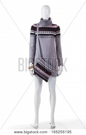Gray winter tunic and handbag. Mannequin wearing tunic with bag. Girl's woolen garment for winter. Cold season clothing in stock.