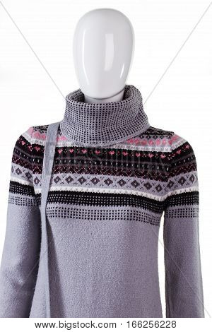Warm sweater with high collar. Mannequin in gray sweatshirt. Girl's new pullover in stock. Sale of winter clothing.