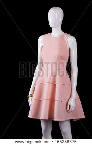 Short evening salmon dress. Light dress on black background. White mannequin wearing stylish dress. Girl's new garment in stock.