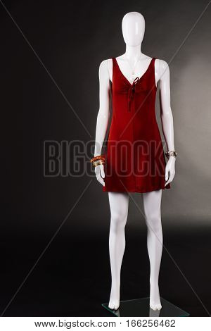 Red keyhole evening dress. Keyhole dress on white mannequin. Stretch clothing of simple design. Woman's attractive evening apparel.