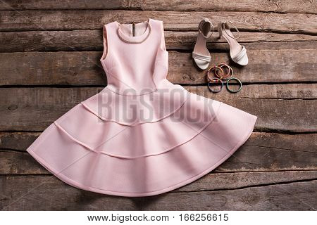 Dress with shoes and necklace. Dress and footwear on shelf. New merchandise in retro shop. Classy clothing on aged showcase.