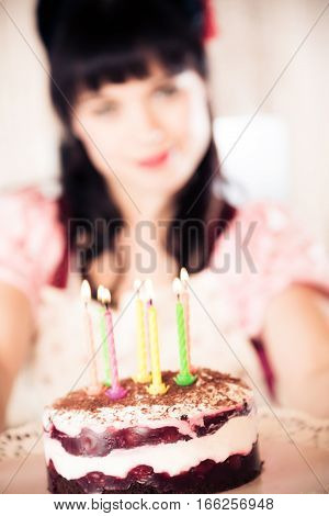 Young woman in vintage dress with birthday cake