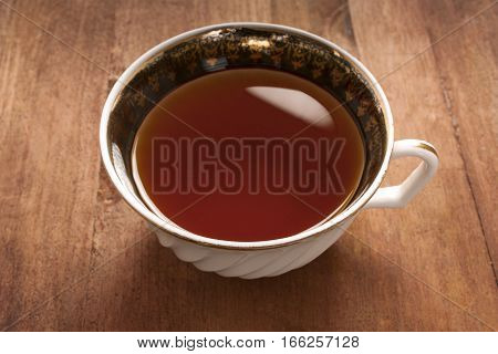 A photo of a vintage tea cup on a dark brown wooden table