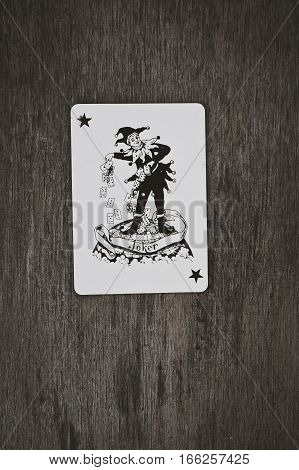 playing cards black joker close up on a wooden table background space for you text game risk abstract.