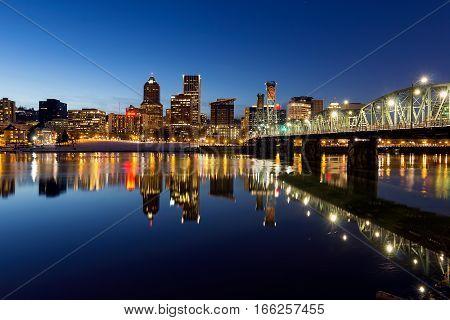 Portland Oregon downtown skyline along Willamette River during blue hour winter night scene