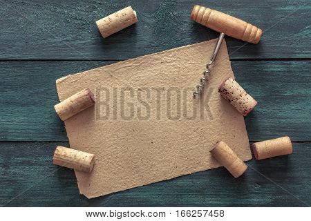 Photo of an old-fashioned corkscrew with corks, shot from above on a dark blue background texture with a piece of old parchment for copyspace. A design template for a wine list or a tasting invitation