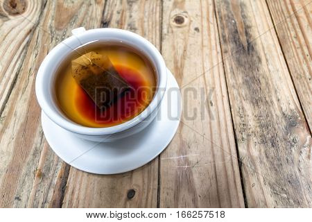 Cup of Hot Tea with Teabag on Grunge Wood Table Background