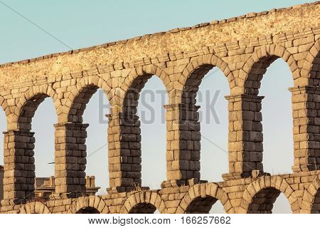 A photo of an ancient Roman aqueduct in Segovia, Spain, slightly toned for a retro look