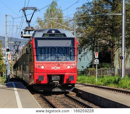Zurich, Switzerland - 20 April, 2016: a train of the Uetliberg railway line arriving to the Triemli station. The Uetliberg railway line is a passenger railway line, which runs from the Zurich main railway station to the summit of Mt. Uetliberg.