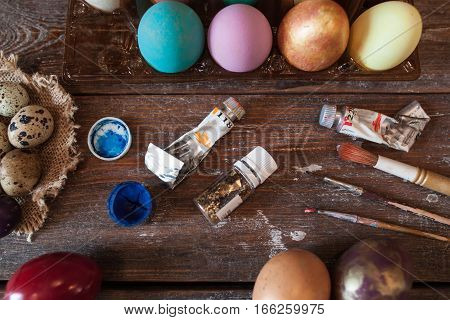 Workplace of artisan before Easter flat lay. Coloring eggs for Easter, top view on table with dye tubes and paintbrushes. Tradition, handmade, art, decoration, creativity concept