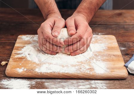 Baker holding raw dough in hands close-up. Cook warming pastry before forming it, original recipe. Homemade bakery, kitchen, cooking process concept