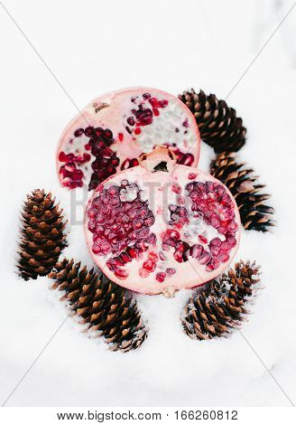 Cut pomegranate on the snow with cones