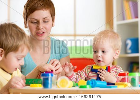Kids boys playing with play clay at home or kindergarten or playschool