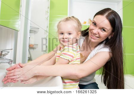 child girl and mother washing hands with soap in bathroom