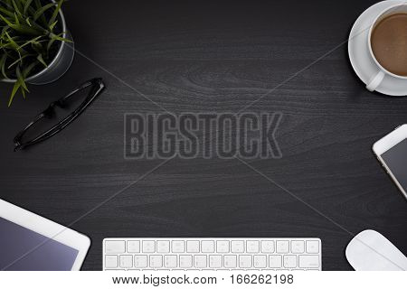 Black office desk table with computer tablet cellphone eye glasses and coffee cup Top view with copy space