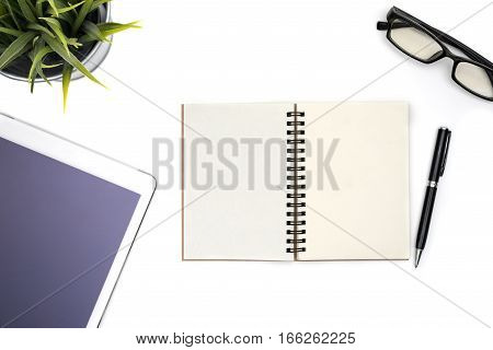 Modern white office desk table with computer tablet pen eye glasses and blank notebook page for input the text in the middle. Top view flat lay.