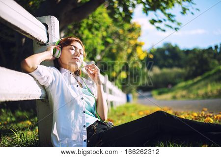 Young women lying in summer grass with headphones listening to music and relaxing Greenery Tone 2017