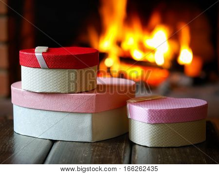 Beautiful boxes - gifts in the form of hearts on fireplace background