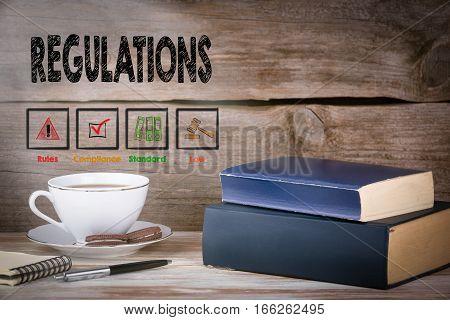 Regulations. Stack of books on wooden desk.