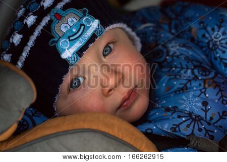 little boy in winter clothes in a child car seat close-up