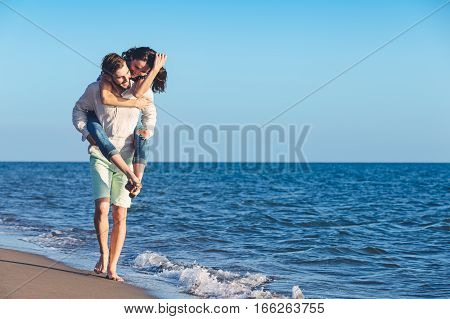 Handsome man giving piggy back to his girlfriend at the beach.