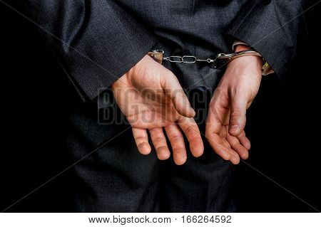 Arrested Businessman In Handcuffs With Hands Behind Back