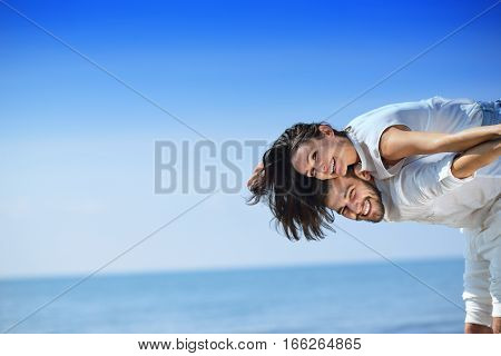 Beach couple laughing in love romance on travel honeymoon vacation summer holidays romance. Young happy people, Asian woman and Caucasian man embracing outdoors on tropical beach in casual wear. poster