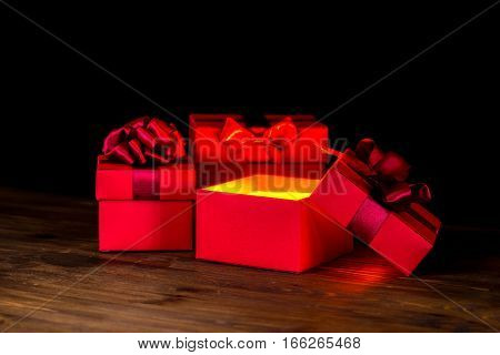 greeting opened box with bow and miracle light on wooden background is isolated on black closeup