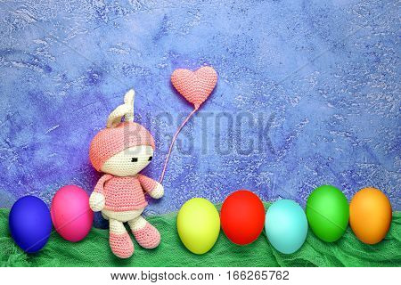 Amigurumi toy easter bunny bunny and crocheted heart shaped balloon with colorful eggs in a row - easter greeting card with copy space