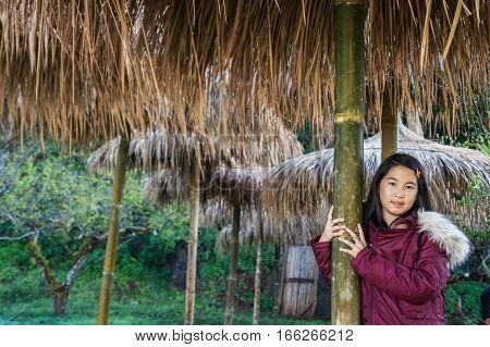 Young girl take portrait under thatched roof on holiday
