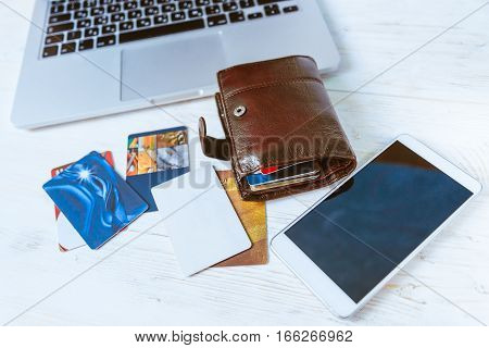 laptop wallet glasses bank cards phone on wooden table