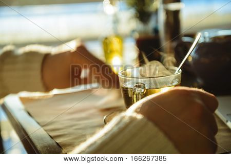 man siting in caffe and drinking tea in front of window with sunset
