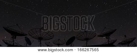 Silhouette satellite dish antenna on top of the building in urban area at night, with stars on clear sky
