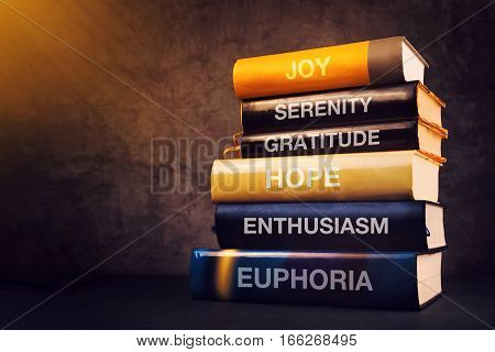 Positive emotions and feelings concept with book titles on library shelf - joy serenity gratitude hope enthusiasm and euphoria
