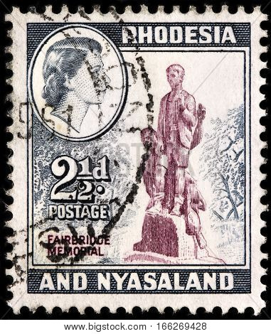 LUGA RUSSIA - SEPTEMBER 18 2015: A stamp printed by RHODESIA AND NYASALAND shows image portrait of Queen Elizabeth II against view of Firebridge Memorial circa 1959